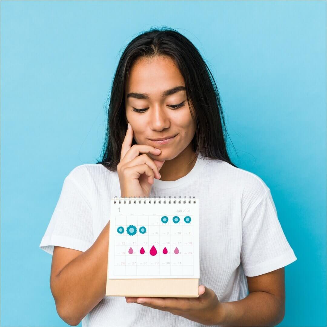 Frau mit Kalender in der Handblickt nachdenklich nach oben vor blauem Hintergrund