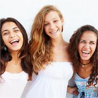 Mädchen lachen gemeinsam vor hellem Hintergrund